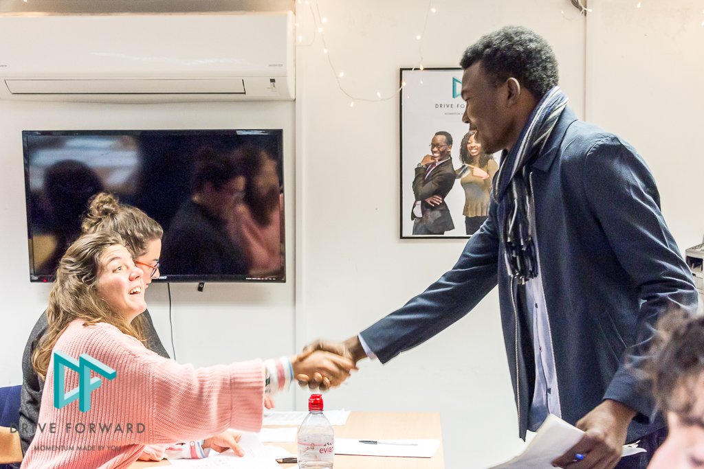 A young man is shaking a female recruiter's hand